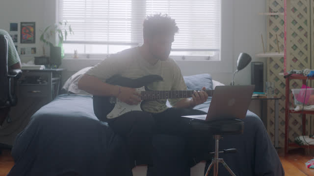 ls of young man learning guitar tabs with his laptop - studying stock videos & royalty-free footage