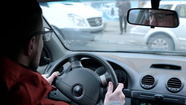 en ung man lär sig att köra bil. - parkera bildbanksvideor och videomaterial från bakom kulisserna