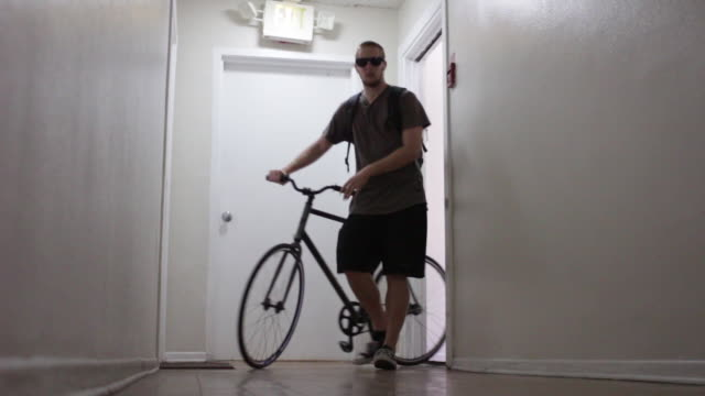 A young man leaving apartment to go on a bike ride.