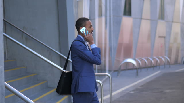 young man leaving building whilst on the phone - mixed race person stock videos & royalty-free footage