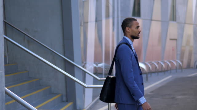 young man leaving the building and checking his bag