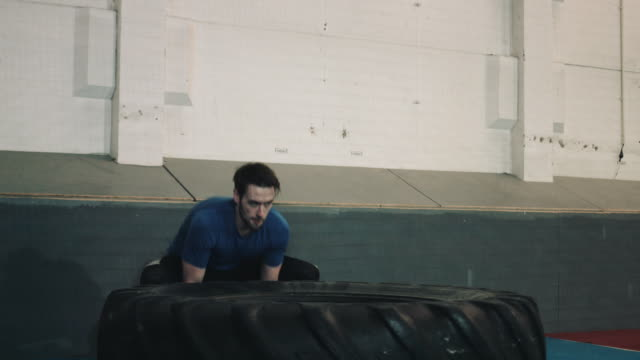 Young man lifting big wheel in bootcamp gym