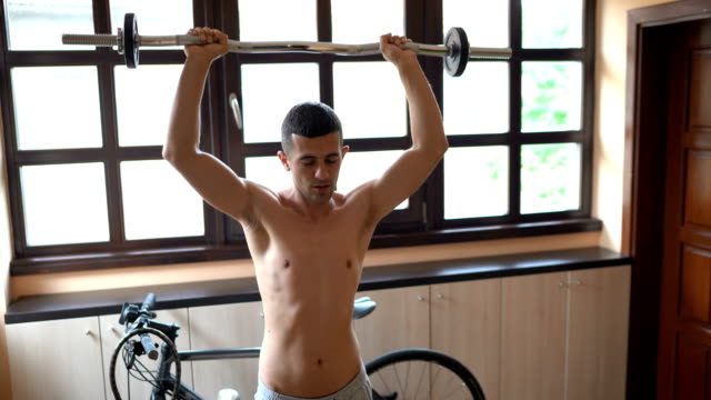young man lifting dumbbells at home - bicep stock videos & royalty-free footage