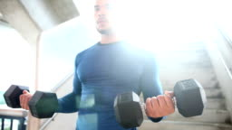 Young man lifting weights to strengthen biceps