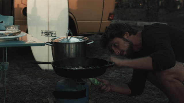 young man lighting camping stove in front of vw bus and surfboard in campground in the south of france. - camping stove stock videos and b-roll footage