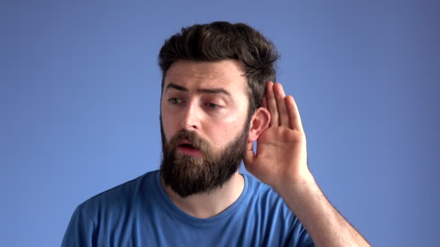 young man listening for gossip on blue background - ascoltare video stock e b–roll