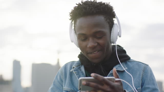 Young man listening music on roof. Changing songs on smartphone