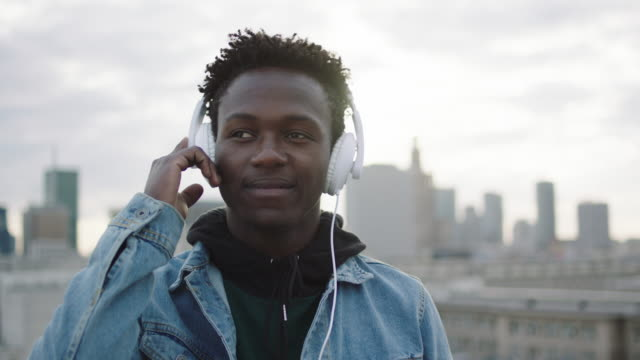 Young man listening music on roof. Holding hand on headphones