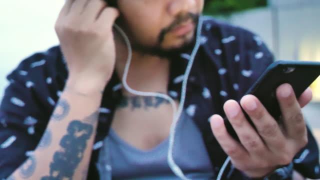Ung man lyssnar musik på stranden