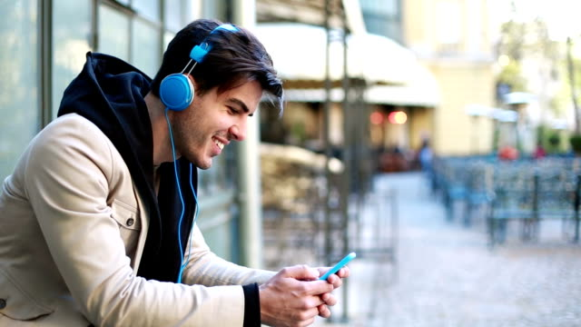 Young man listening music outdoor and texting