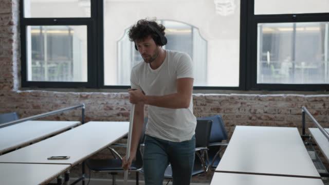vídeos y material grabado en eventos de stock de joven escuchando música con auriculares, bailando mientras barre el piso de una oficina - barrer