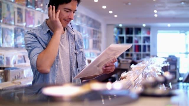 vídeos y material grabado en eventos de stock de joven escuchas discos en la tienda de vinilo - auriculares aparato de información