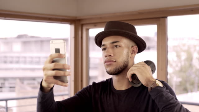 A young man listening to music from his smart phone on a wireless portable speaker