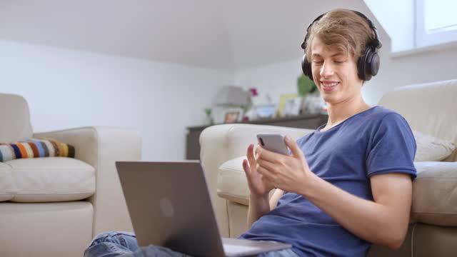 junger mann hört musik auf seinen kopfhörern, während er an seinem laptop arbeitet - junger mann allein stock-videos und b-roll-filmmaterial