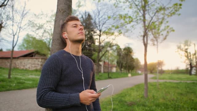 Young man listening to music on mobile phone, using headphones outdoors, in nature, leaning against the tree