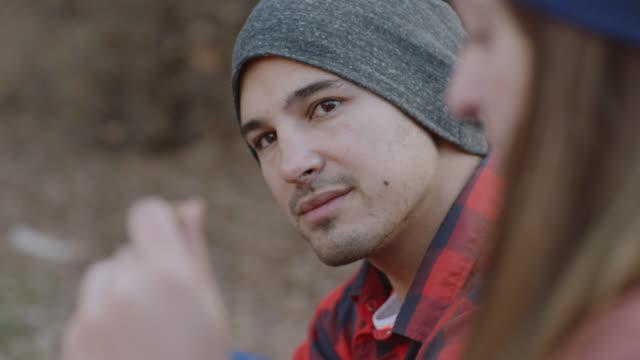 vídeos de stock, filmes e b-roll de cu. young man listens to friends talk and nods on camping trip. - fire natural phenomenon