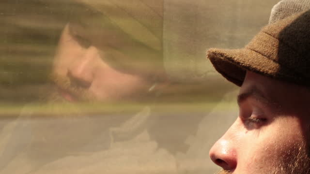 Young man listens to music on train ride and stares at his reflection in the window.