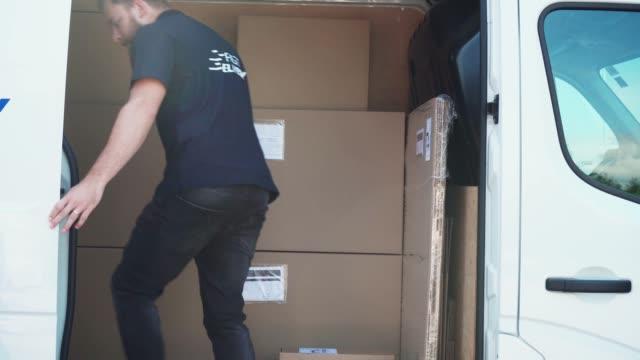 stockvideo's en b-roll-footage met jonge man laden van een busje met pakketten - bestelwagen