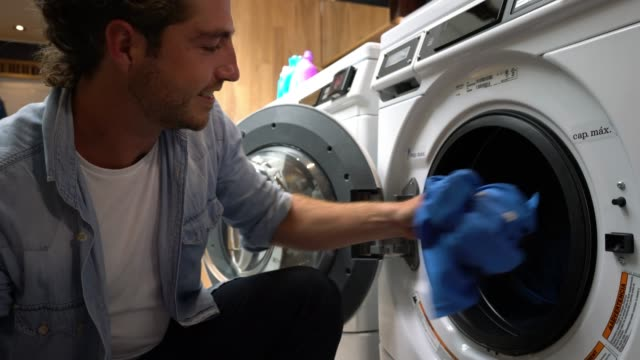 young man loading washing machine at a laundromat and then adjusting preferences on machine - launderette stock videos & royalty-free footage