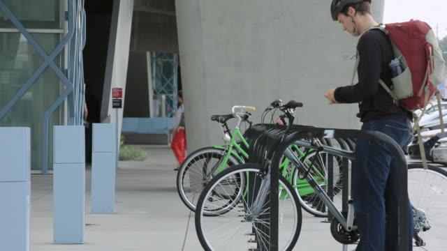 vídeos y material grabado en eventos de stock de young man locking bike - cerrar con llave