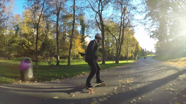 a young man longboard skateboarding downhill in a city park wearing a suit and talking on his mobile phone. - 乗る点の映像素材/bロール