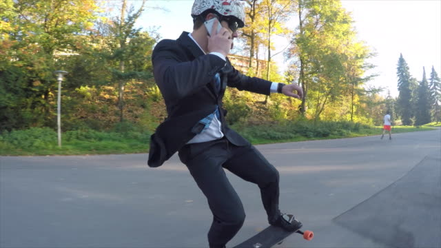 a young man longboard skateboarding downhill in a city park wearing a suit and talking on his mobile phone. - safety stock-videos und b-roll-filmmaterial