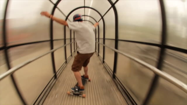 a young man longboard skateboarding downhill in a city through a tunnel. - time-lapse - individuality stock videos & royalty-free footage