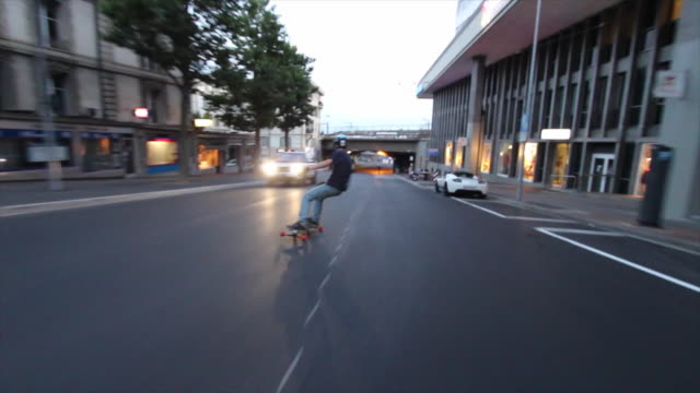 a young man longboard skateboarding downhill in a city. - verboten stock-videos und b-roll-filmmaterial