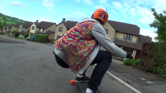 a young man longboard skateboarding downhill in a residential neighborhood. - time-lapse - sports helmet stock videos & royalty-free footage