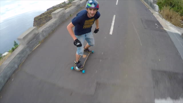 a young man longboard skateboarding downhill with a helmetcam pov. - wearable kamera stock-videos und b-roll-filmmaterial
