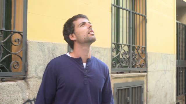 vídeos y material grabado en eventos de stock de a young man lookin up and smiling when he see something - mirar hacia arriba