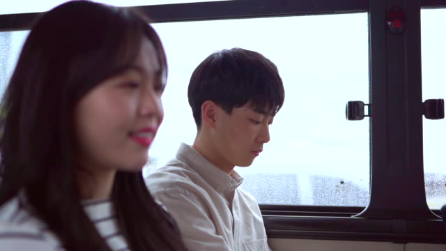 a young man looking at a young woman in a bus - south korea couple stock videos & royalty-free footage
