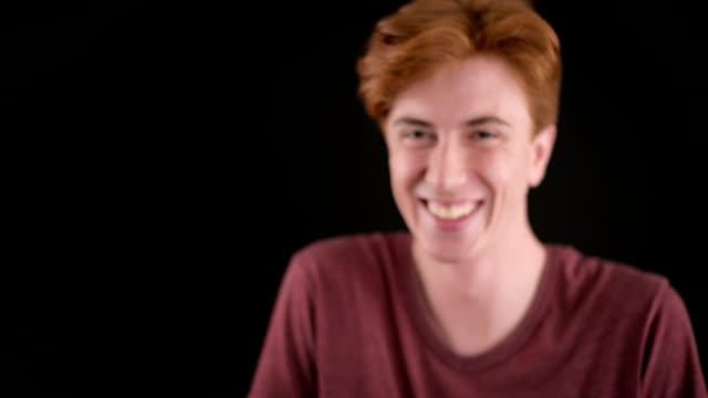 junger mann, blick in die kamera und lächelnd - 20 24 jahre stock-videos und b-roll-filmmaterial