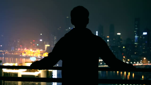 vídeos y material grabado en eventos de stock de hombre joven busca en la noche de la ciudad - un solo hombre