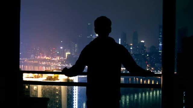 ung man tittar på staden scen på natten - fönsterrad bildbanksvideor och videomaterial från bakom kulisserna