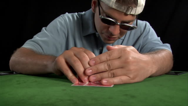 Young man looking at hand in game of Texas Hold'em / going all in by sliding chips across table