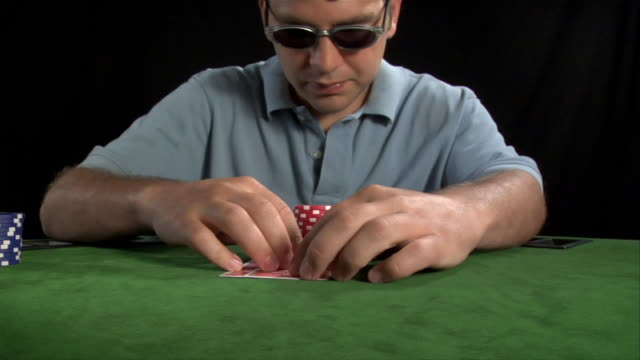 vídeos de stock, filmes e b-roll de young man looking at hand in game of texas hold'em / placing chips in front of camera - texas hold 'em
