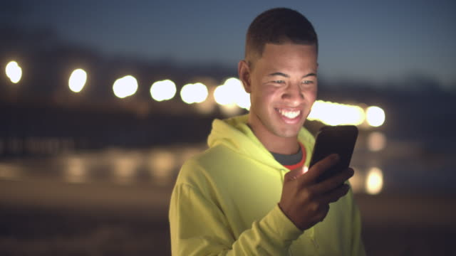 young man looking at his phone at night - sweatshirt stock videos & royalty-free footage