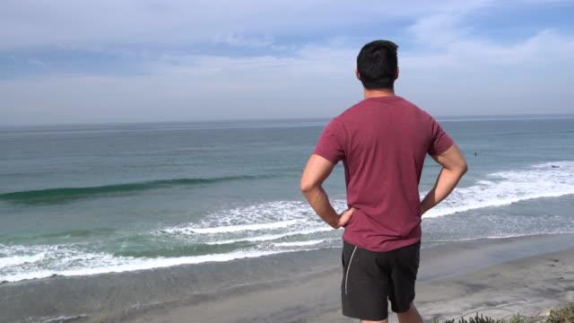 ms rv young man looking at the ocean - 腰に手を当てる点の映像素材/bロール