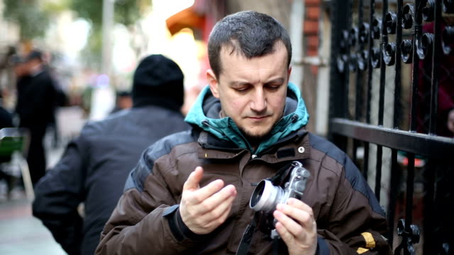 Young man looking his digital camera
