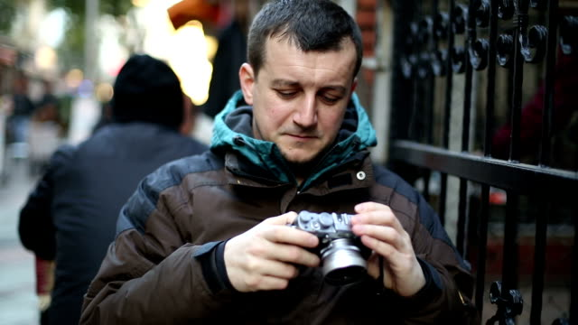 vidéos et rushes de jeune homme regardant son appareil photo numérique - seulement des jeunes hommes