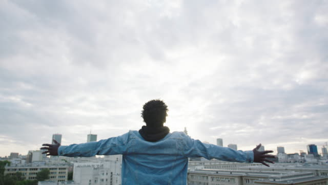 Young man looking on city with opened arms