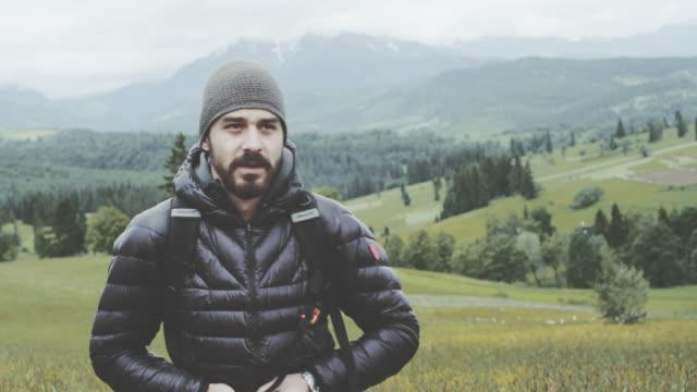 junger mann sucht in der ansicht. wiese in bergen - handsome people stock-videos und b-roll-filmmaterial
