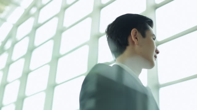 CU Young man looking out of window in modern office.