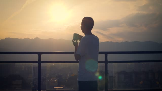 young man looking sunset and drinking cup of coffee - only men stock videos & royalty-free footage