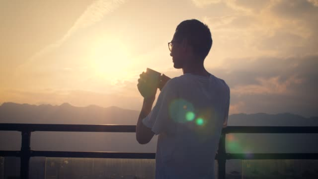 vídeos y material grabado en eventos de stock de joven mirando puesta de sol y bebiendo taza de café - taza de café