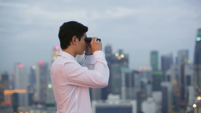 MS young man looking through binoculars at cityscape.