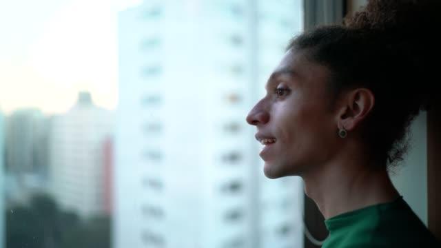 junger mann schaut durch fenster - vorhersagen stock-videos und b-roll-filmmaterial