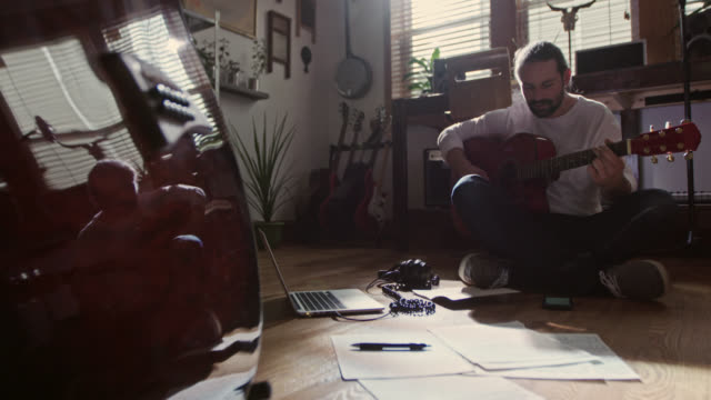 vídeos de stock e filmes b-roll de ws. young man looks at music on smartphone and plays along with acoustic guitar. - músico