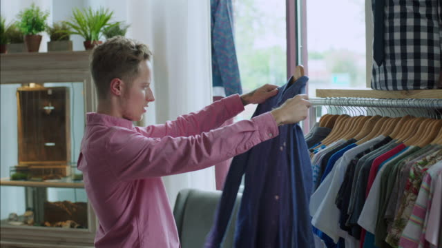 Young man looks at shirt and employee approaches offering assistance in modern clothing store